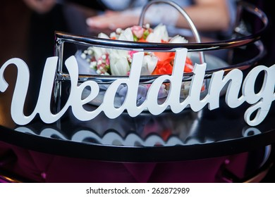 Word Wedding and bridal bouquet lying on the bar table in the background hands of the bride and groom
