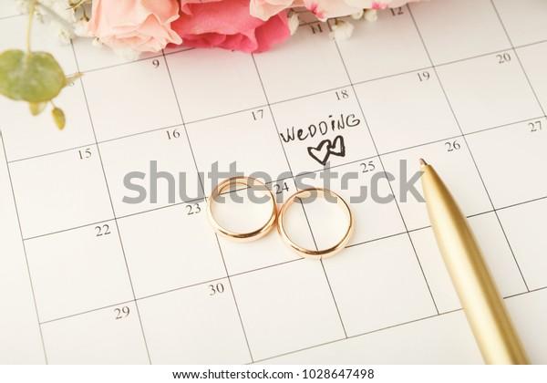 Wordウエディング、2つのハートと金のリング、カレンダーに甘いバラのブーケ。愛、招待、広告、ロマンチックな背景コンセプト、コピー用スペース
