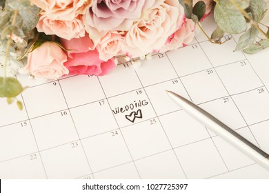 Word wedding and two hearts on calendar with sweet rose bouquet. Love, invitation, advertisement, romantic background concept, copy space