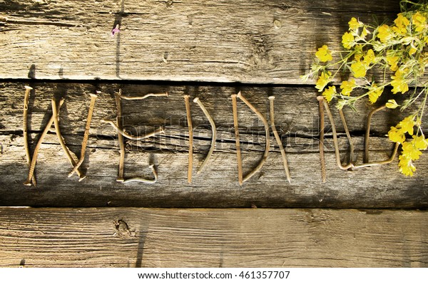the word wedding written by nails on the old wooden boards with a bouquet of yellow flowers