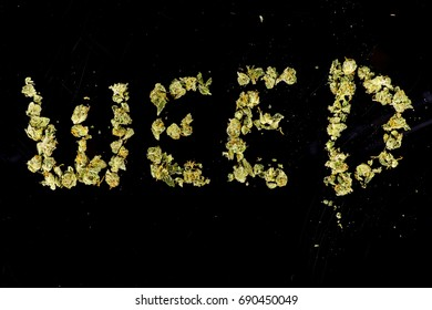 The word weed spelled out with marijuana buds on black background