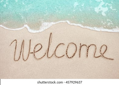 Word Welcome handwritten on sandy beach with soft wave of blue ocean on background.