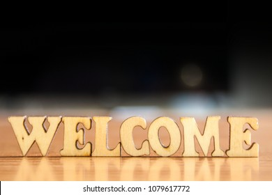 The word 'welcome' made of wooden letters. wood inscription on table and dark black background