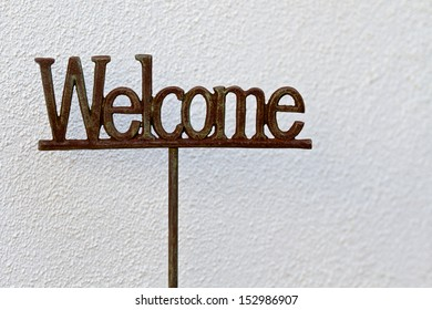 The word Welcome in metal against a white textured background.