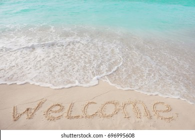 Word WELCOME on beach sand. Summer vacation concept