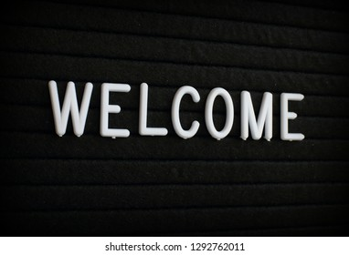 The word Welcome in white plastic letters on a black letter board