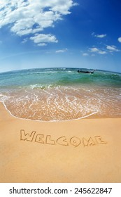 """The word """"Welcome"""" written on the sand against the sea. Phuket island, Thailand"""