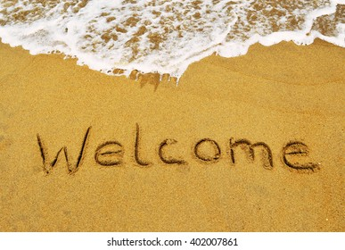 The word Welcome written in the sand at the beach