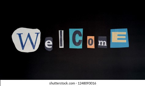 """The word """"Welcome""""in cut out letters blackmail style in black background"""