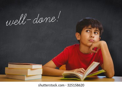 The word well-done! and thoughtful boy reading book in library against blackboard