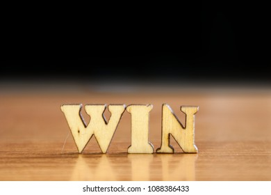 The word 'win' made of wooden letters. wood inscription on table and dark black background