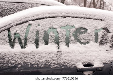 "The word ""winter"" etched into snow on car window"