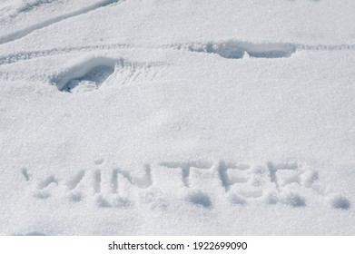 The word winter is written, drawn by a man on white fresh snow. Photography, top view, concept.