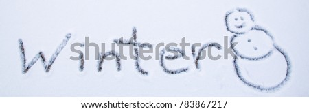 The word winter written in snow on sidewalk with a smiling snowman Kentucky USA 2018