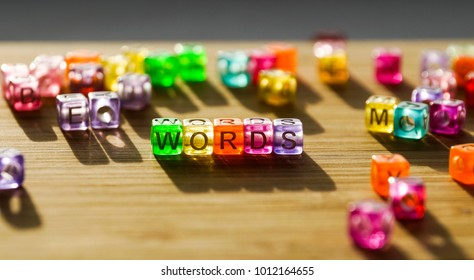 Word words from a square of colored blocks on a wooden surface.
