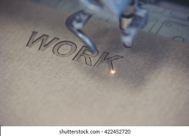 """Word """"Work"""" being engraved with a laser from a cardboard material"""