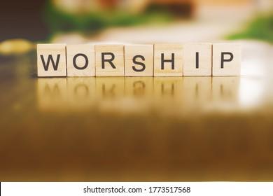 The word WORSHIP written in wood block.
