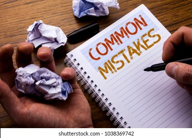 Word, writing Common Mistakes. Concept for Common Concept written on notebook notepad note paper on wooden background with folded paper meaning thinking for idea. Man hand and marker.