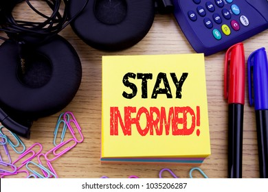 Word, writing Stay Informed. Business concept for Be Awareness Or Awake written on sticky note paper on wooden background. With calculator and pen marker and headphones