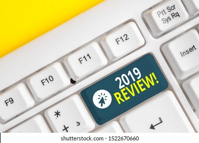 Word writing text 2019 Review. Business concept for remembering past year events main actions or good shows White pc keyboard with empty note paper above white background key copy space.