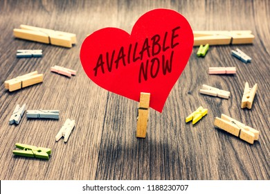 Word writing text Available Now. Business concept for Handy Eligible Today Present Bachelor Here on Board Accessible Clothespin holding red paper heart several clothespins wooden floor romance.