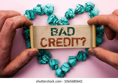 Word writing text Bad Credit Question. Business concept for Low Credit Finance Economic Budget Asking Questionaire written on Cardboard Paper Holding by man plain background on Heart Paper Balls.