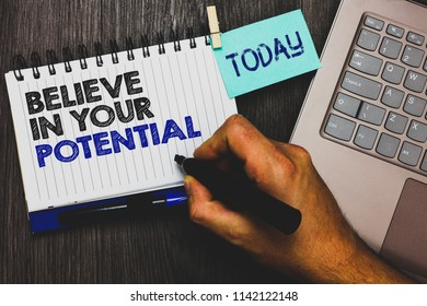 Word writing text Believe In Your Potential. Business concept for Have self-confidence motiavate inspire yourself Paperclip grip sticky note with text hand hold pen computer on wooden desk.