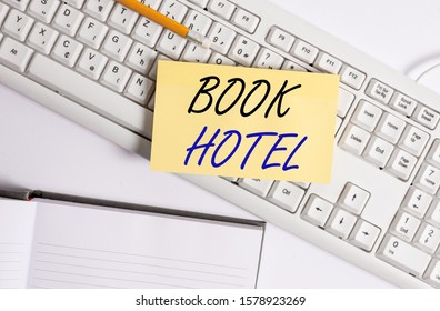 Word writing text Book Hotel. Business concept for an arrangement you make to have a hotel room or accommodation White pc keyboard with empty note paper and paper clips above white background.