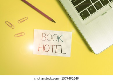 Word writing text Book Hotel. Business concept for an arrangement you make to have a hotel room or accommodation Trendy metallic laptop clips pencil squared paper sheet colored background.