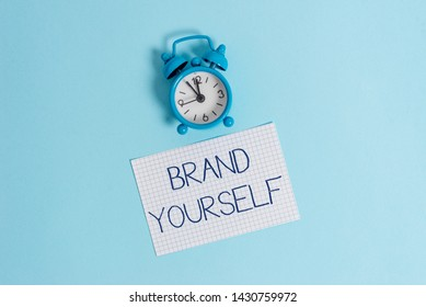 Word writing text Brand Yourself. Business concept for Develop a unique professional identity Personal product Vintage alarm clock wakeup squared blank paper sheet colored background.