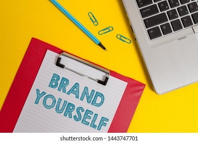 Word writing text Brand Yourself. Business concept for Develop a unique professional identity Personal product Open laptop clipboard blank paper sheet marker clips colored background.