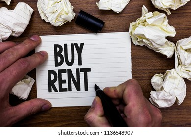 Word writing text Buy Rent. Business concept for choosing between purchasing something or paying for usage Man holding marker notebook page crumpled papers several tries mistakes.