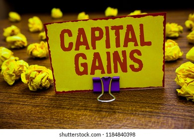 Word writing text Capital Gains. Business concept for Bonds Shares Stocks Profit Income Tax Investment Funds Clip holding yellow paper note crumpled papers several tries mistakes.