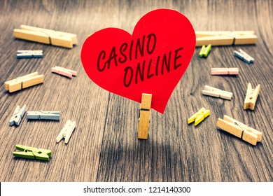 Word writing text Casino Online. Business concept for Computer Poker Game Gamble Royal Bet Lotto High Stakes Clothespin holding red paper heart several clothespins wooden floor romance.