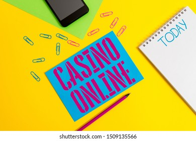 Word writing text Casino Online. Business concept for Computer Poker Game Gamble Royal Bet Lotto High Stakes Blank spiral notepad pencil clips smartphone paper sheets color background.