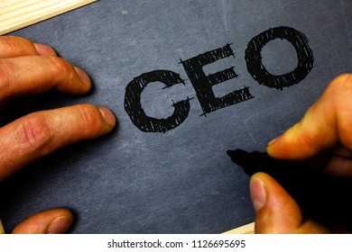 Word writing text Ceo. Business concept for Chief Executive Officer Head Boss Chairperson Chairman Controller Man hold holding black marker markers notebook wood wooden background.