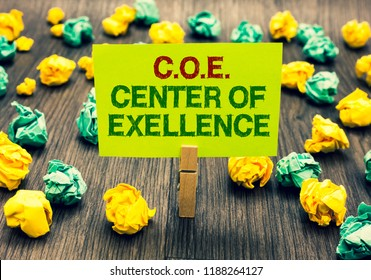 Word writing text C.O.E Center Of Excellence. Business concept for being alpha leader in your position Achieve Clothespin holding yellow note paper crumpled papers several tries mistakes.