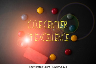 Word writing text Coe Center Of Excellence. Business concept for being alpha leader in your position Achieve Round Flat shape stones with one eraser stick to old chalk black board.