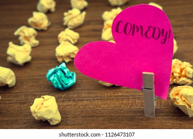 Word writing text Comedy Call. Business concept for Fun Humor Satire Sitcom Hilarity Joking Entertainment Laughing Clothespin holding pink heart paper crumpled papers ideas mistakes trials.