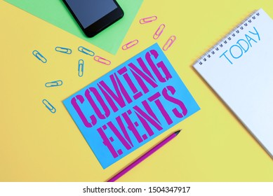 Word writing text Coming Events. Business concept for Happening soon Forthcoming Planned meet Upcoming In the Future Blank spiral notepad pencil clips smartphone paper sheets color background.