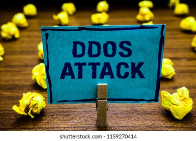 Word writing text Ddos Attack. Business concept for perpetrator seeks to make network resource unavailable Clothespin holding blue paper note crumpled papers several tries mistakes.