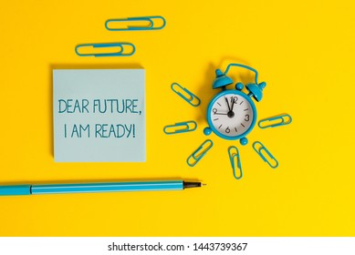 Word writing text Dear Future I Am Ready. Business concept for Confident to move ahead or to face the future Metal alarm clock wakeup clips ballpoint notepad colored background.