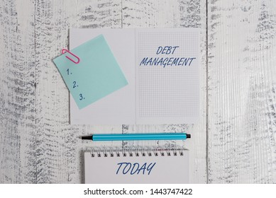 Word writing text Debt Management. Business concept for The formal agreement between a debtor and a creditor Open squared spiral notepad clip note highlighter lying old wooden background.