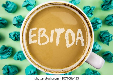Word writing text Ebitda. Business concept for Earnings before tax is measured to evaluate company performance written on Tea in White Cup within Crumpled Paper Balls on plain background.