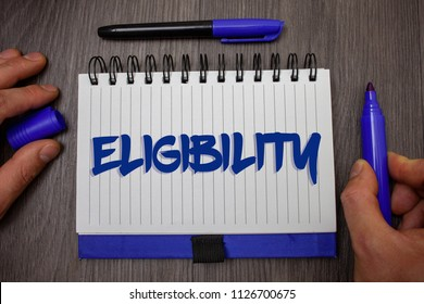 Word writing text Eligibility. Business concept for State of having the right for doing or obtain something Proper Man hold holding blue marker notebook page paper ideas wooden background.