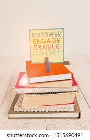 Word writing text Empower Engage Enable Enhance. Business concept for Empowerment Leadership Motivation Engagement pile stacked books notebook pin clothespin colored reminder white wooden.