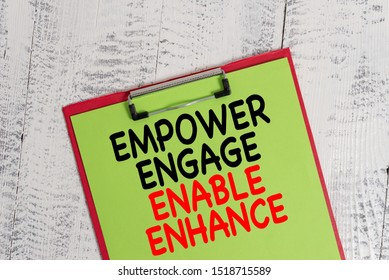 Word writing text Empower Engage Enable Enhance. Business concept for Empowerment Leadership Motivation Engagement Colored clipboard blank paper sheet old retro wooden vintage background.