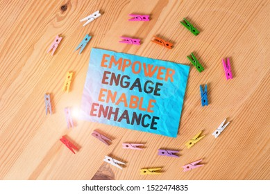 Word writing text Empower Engage Enable Enhance. Business concept for Empowerment Leadership Motivation Engagement Colored clothespin papers empty reminder wooden floor background office.