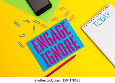 Word writing text Engage Ignore. Business concept for Silent Treatment Manipulative Punishment Sulking Shunning Blank spiral notepad pencil clips smartphone paper sheets color background.
