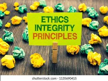 Word writing text Ethics Integrity Principles. Business concept for quality of being honest and having strong moral Clothespin holding yellow note paper crumpled papers several tries mistakes.
